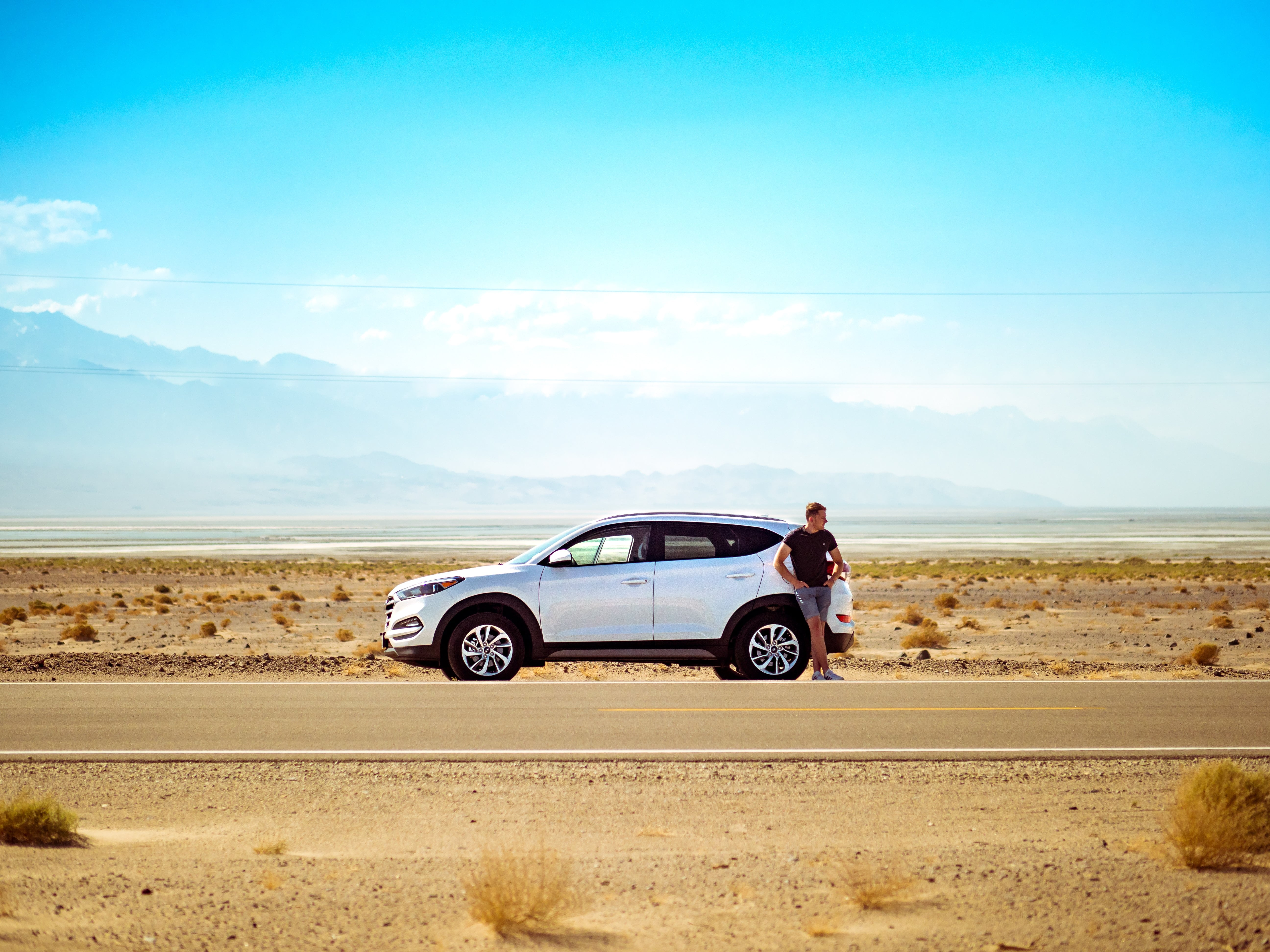 A person stands in front of a car on a stretch of road in a dessert landscape.