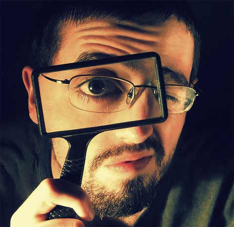 Man using a magnifying glass to read through terms and conditions of a loan document
