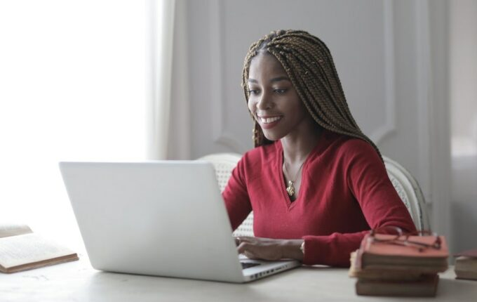 A woman sits at her desk, with her laptop in front of her.