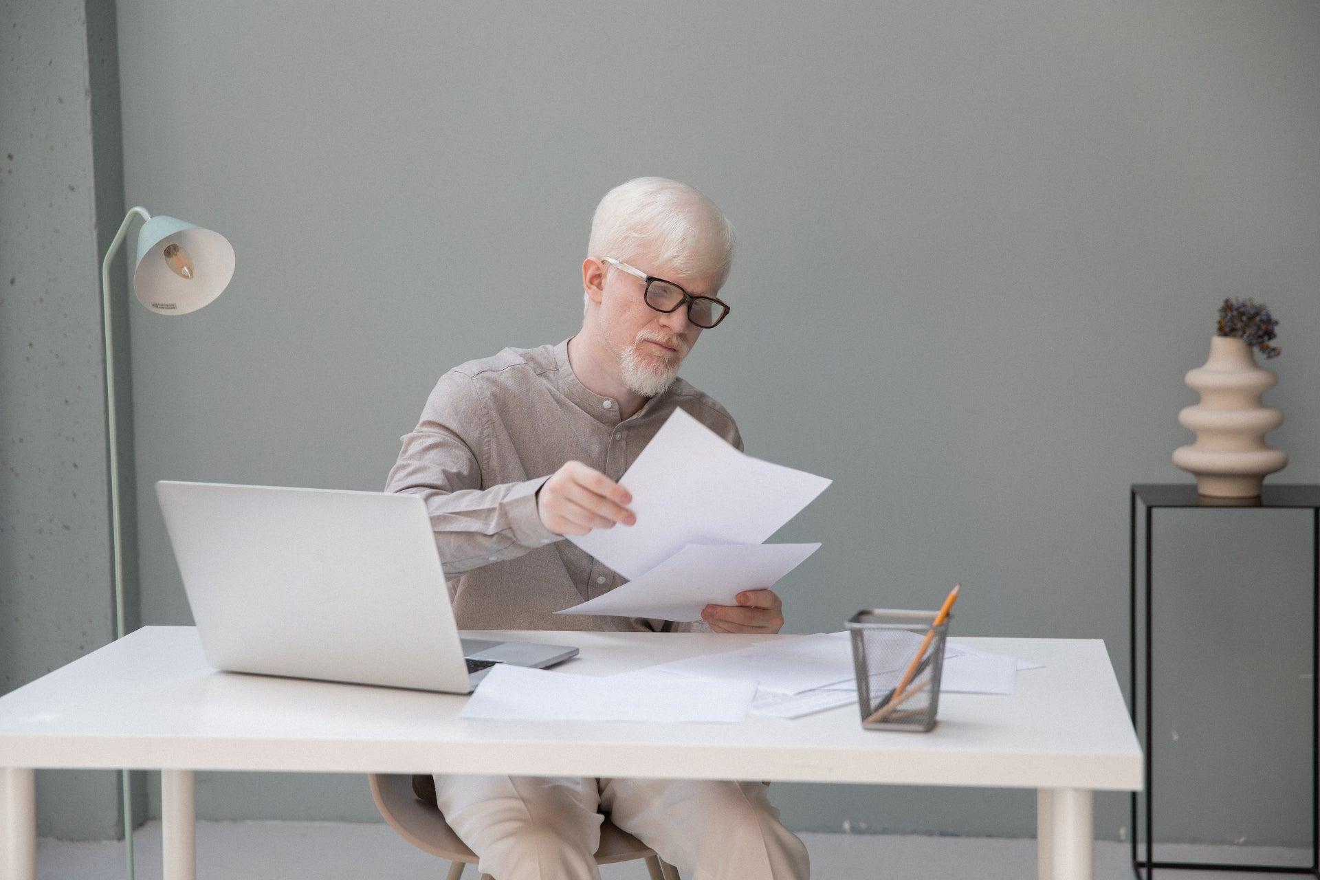 Un hombre de cabello blanco y barba blanca se sienta en un escritorio blanco con una computadora portátil y mira varios trozos de papel.