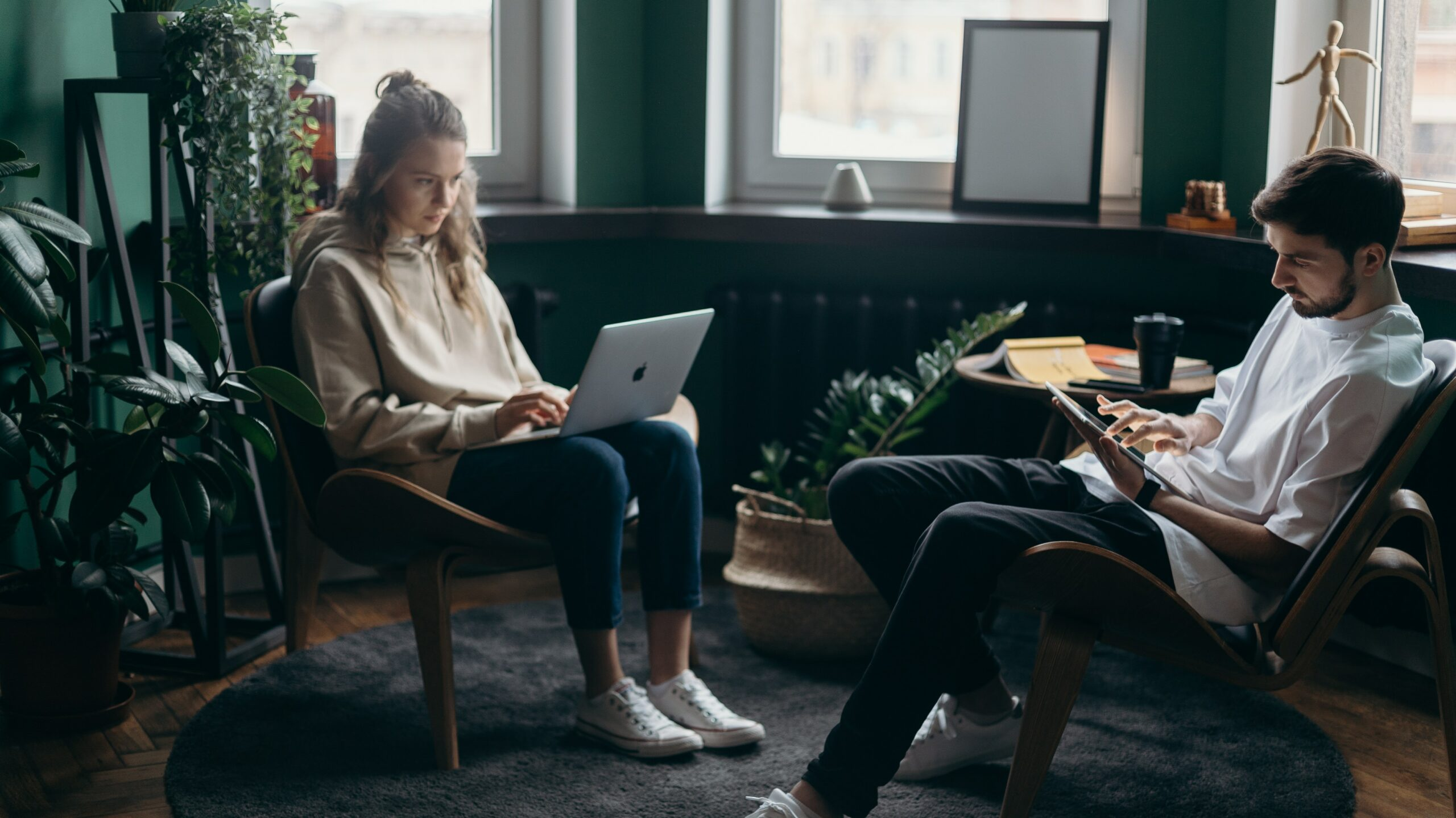 Two young white people sit in a dark green room. One has a laptop and the other is looking at a tablet to find out all their debts.