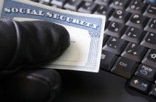 Man's hand holding Social Security card. Computer theft on laptop.