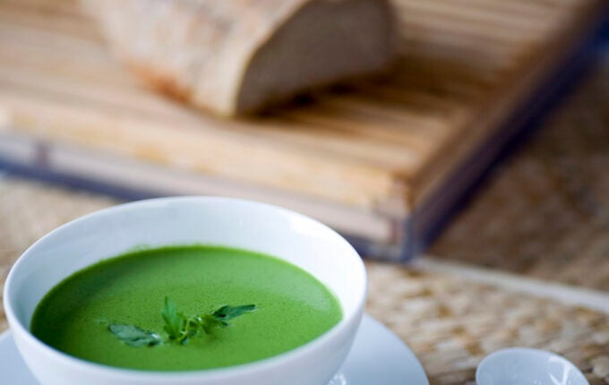 A  pure white bowl of vivid green soup with crusty home made bread behind makes for a tempting image of healthy eating. Shallow DOF with focus on soup. Other tasty soups and more  below: