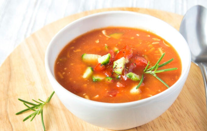 Fresh delicious tasty cold tomato soup gazpacho in white bowl with spoon on wooden board, closeup, horizontal