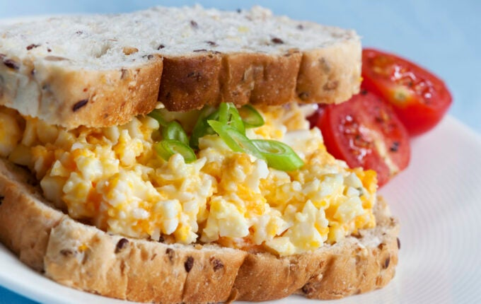 Sandwich with egg salad.  Wholewheat bread, with cherry tomatoes on the side.  Shallow DOF.