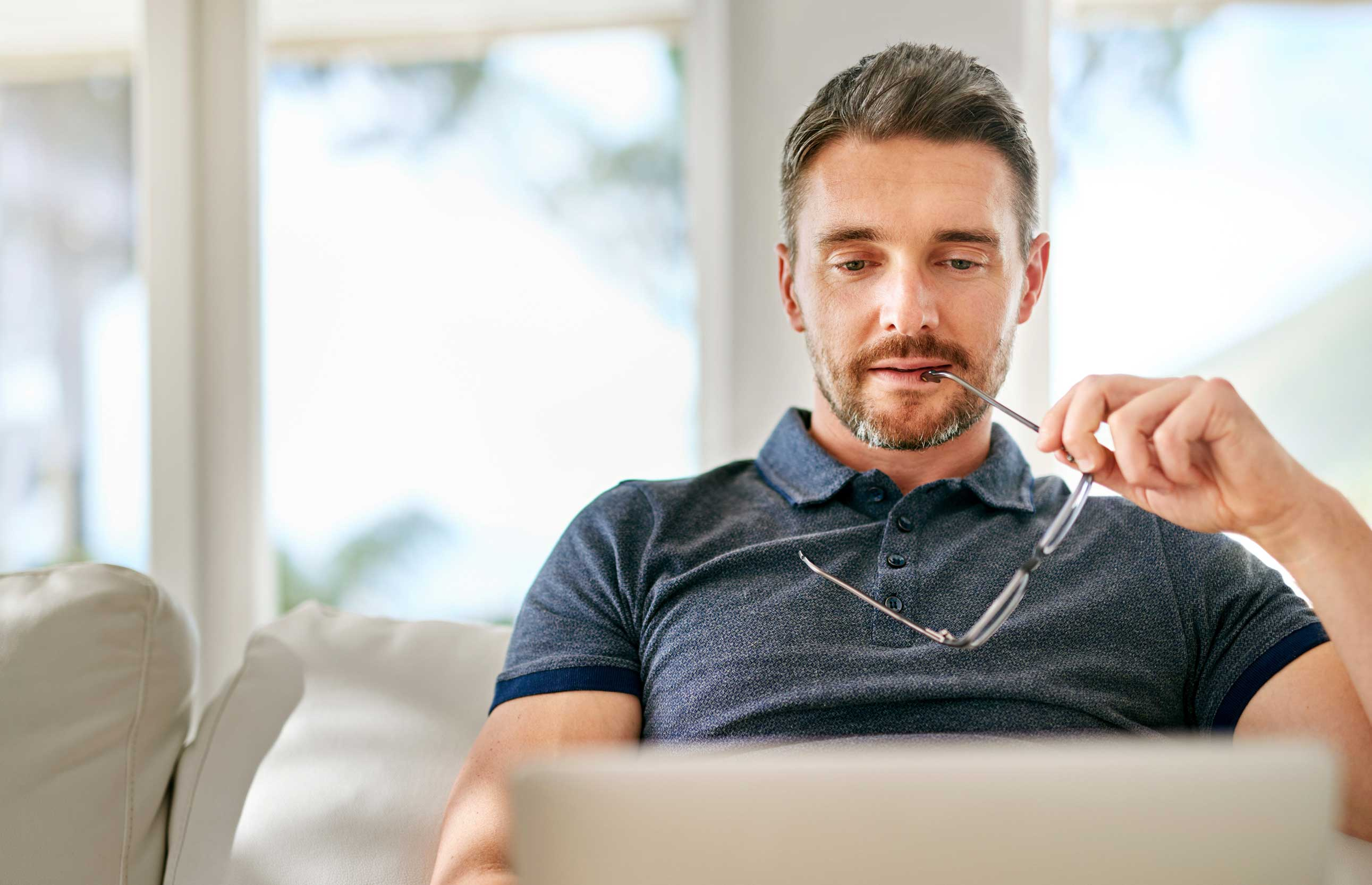 Man at laptop computer contemplating how the new tax laws affect him
