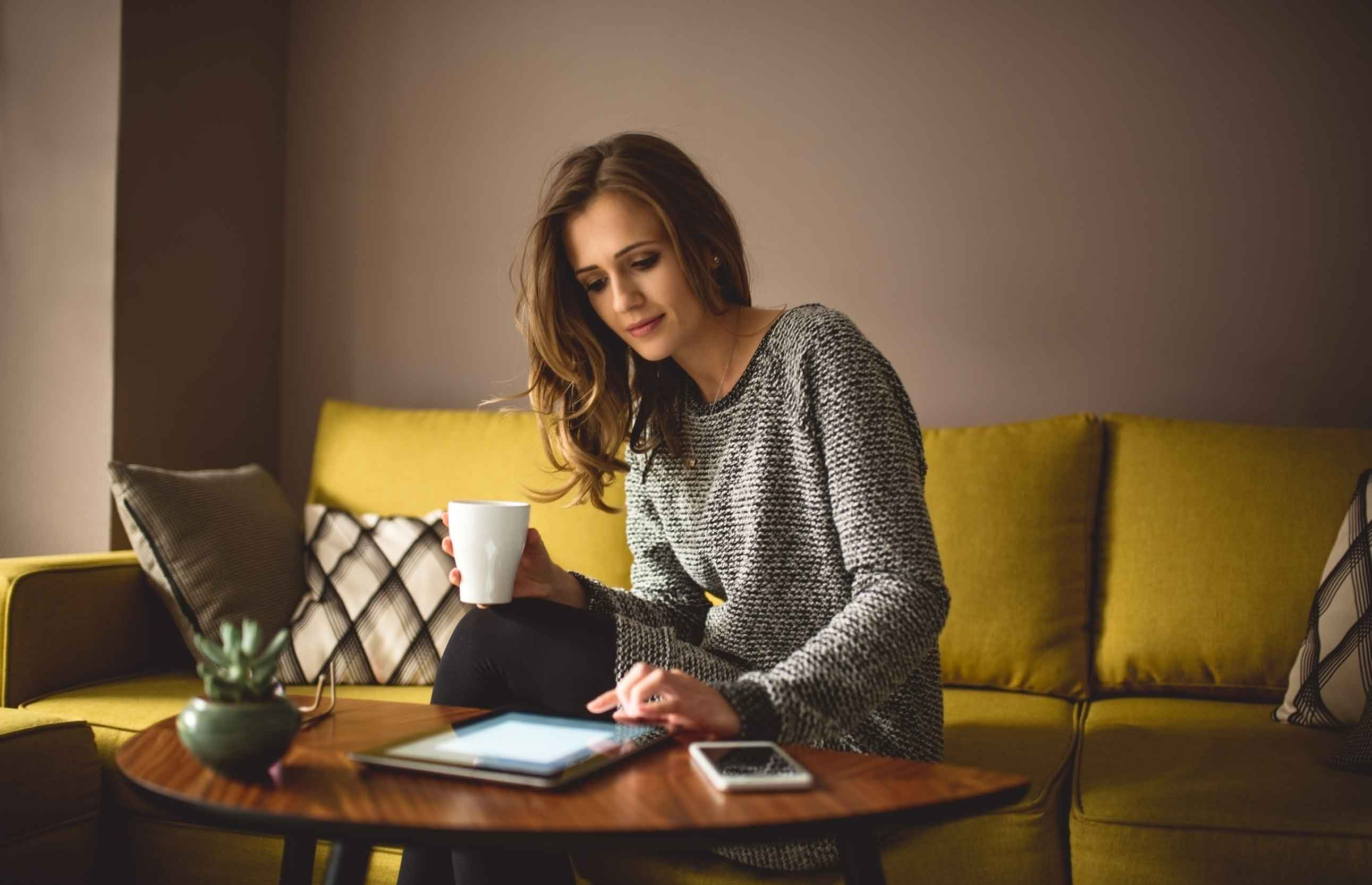 Woman looking at laptop ealizing how a 15 year fixed mortgage will save her money
