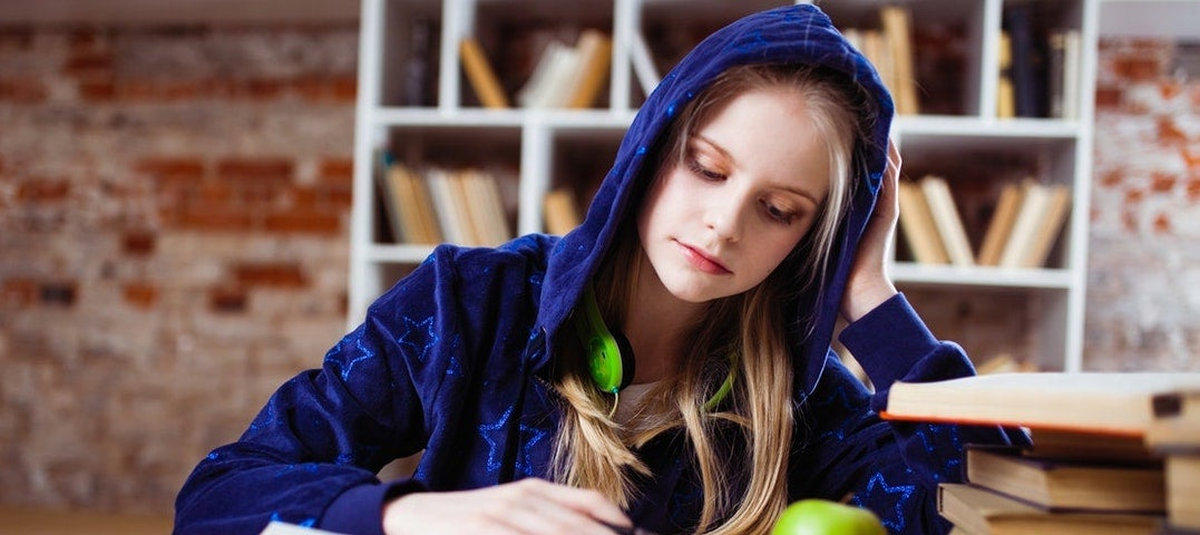 A young blond woman wearing a blue hoodie with the hood on and bright green headphones sits on a chair near a bookshelf.