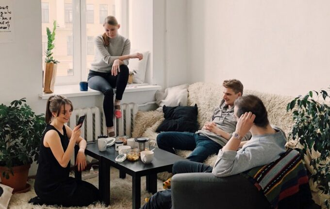 Four roommates sit together in their living room, chatting.
