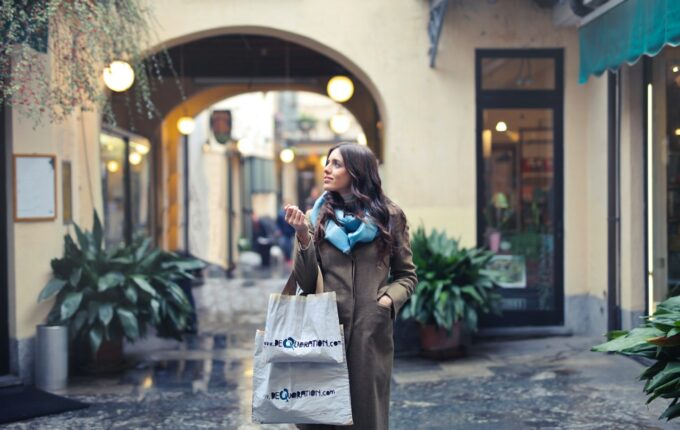 A woman wearing a long coat and a blue scarf holds several shopping bags as she looks off to the side and smiles