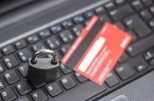 High angle view of credit card with security lock on computer keyboard. Computer keyboard is in full frame position, defocussed. Focus on lock. Horizontal composition. Image developed from RAW format.