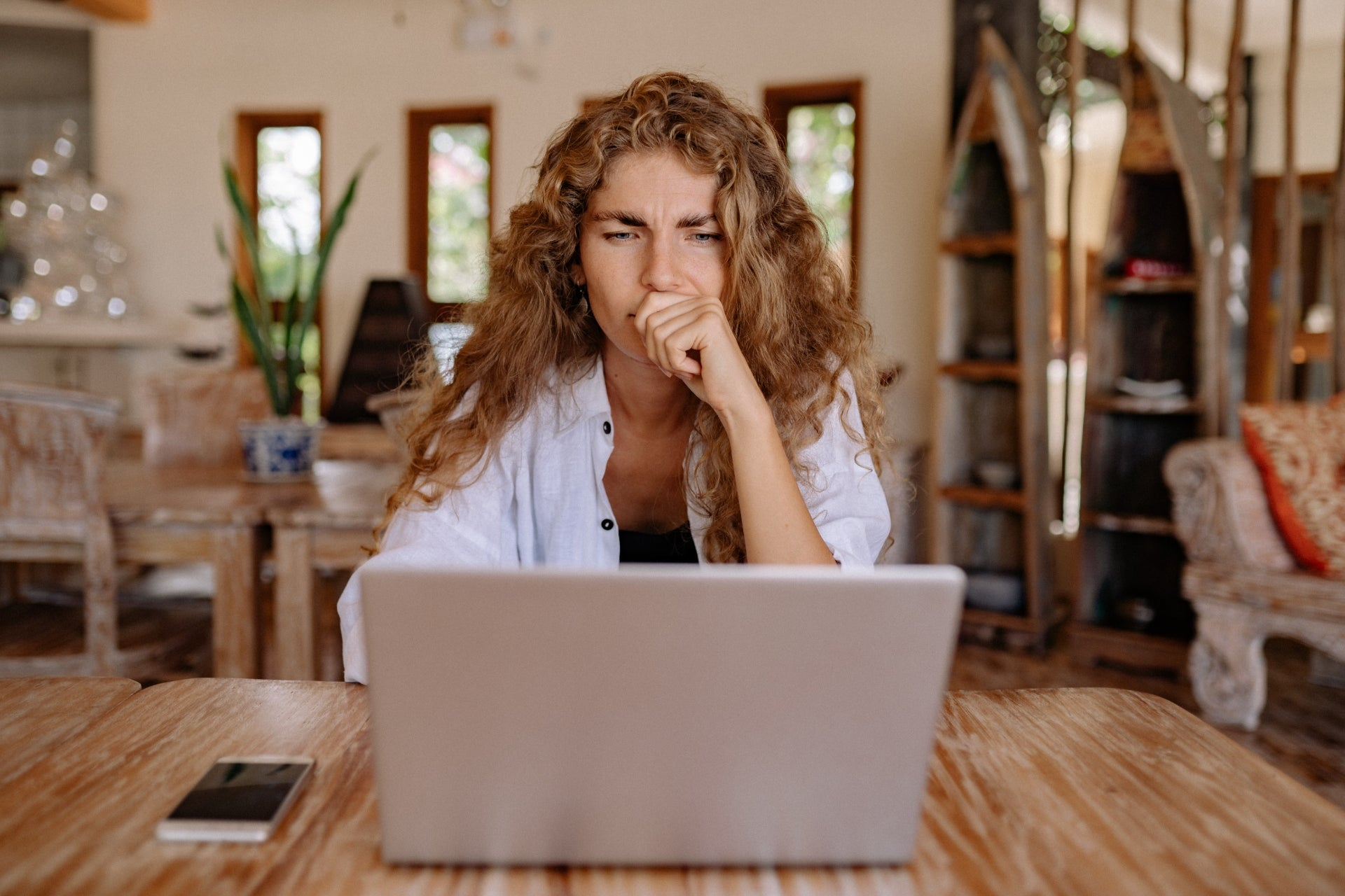A woman looks at her laptop computer with a thoughtful look on her face.