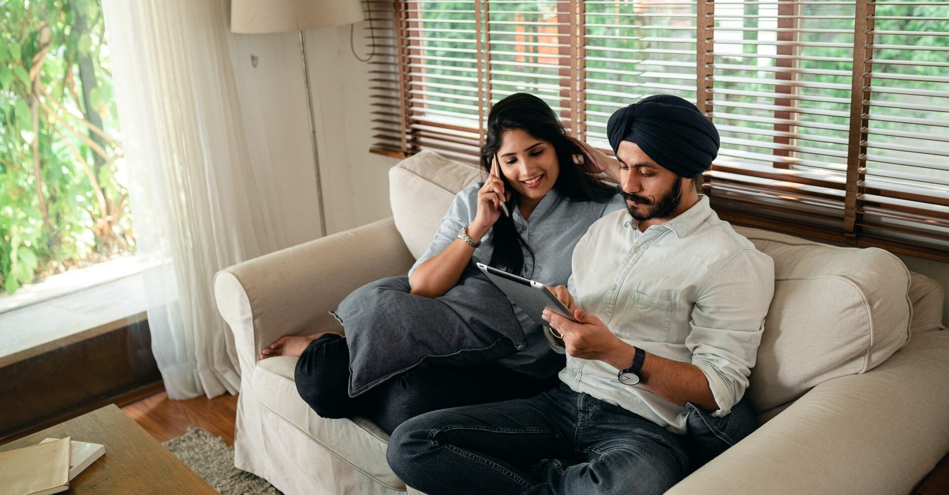 A couple sits on a loveseat smiling and looking at a tablet together