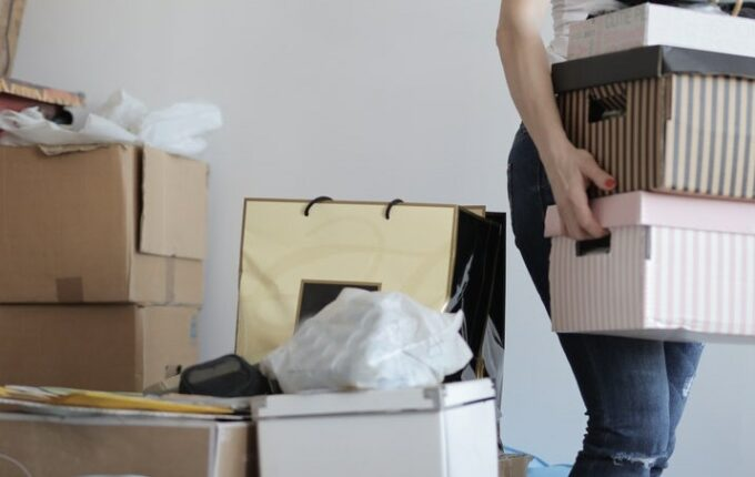 A woman is holding a stack of boxes in her arms, with a pile of boxes behind her.