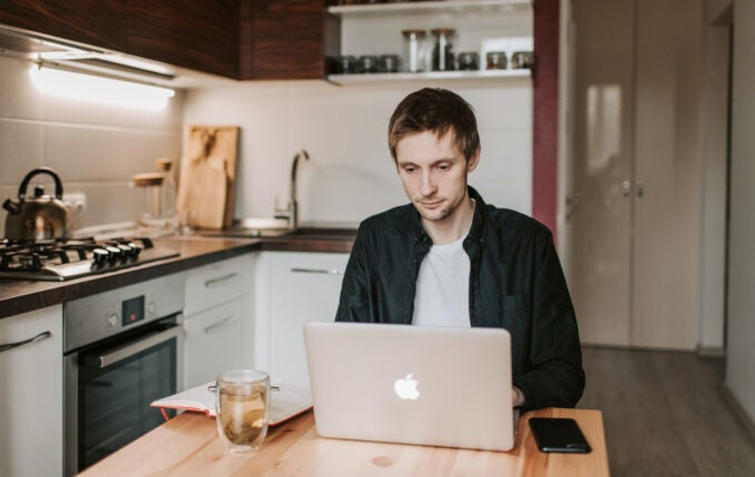 A young man sits at his kitchen table on his laptop learning how to do taxes yourself.