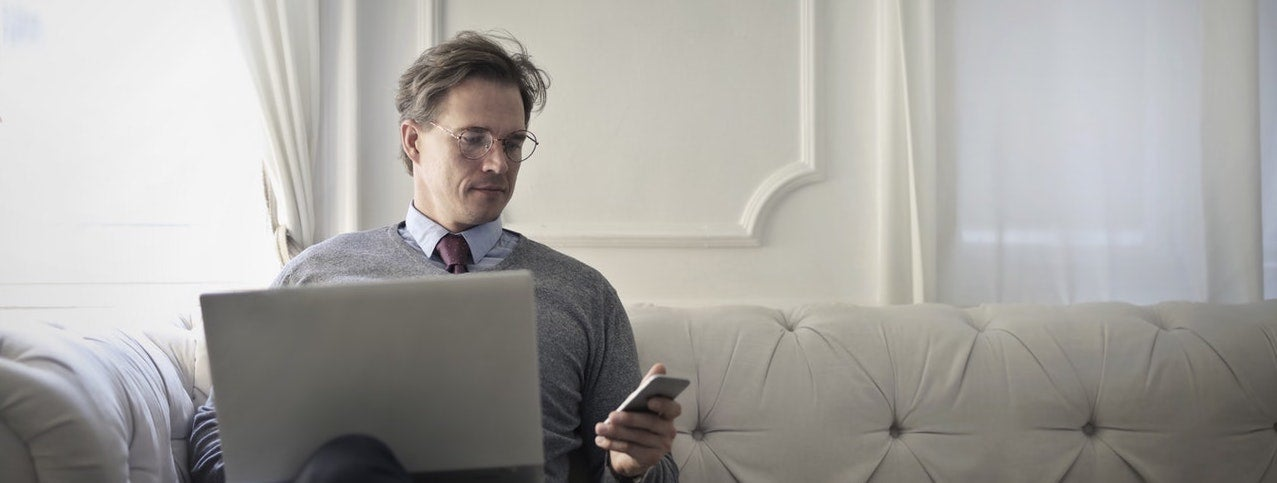A man sits on a couch with his laptop in his lap, looking at the phone in his hand.