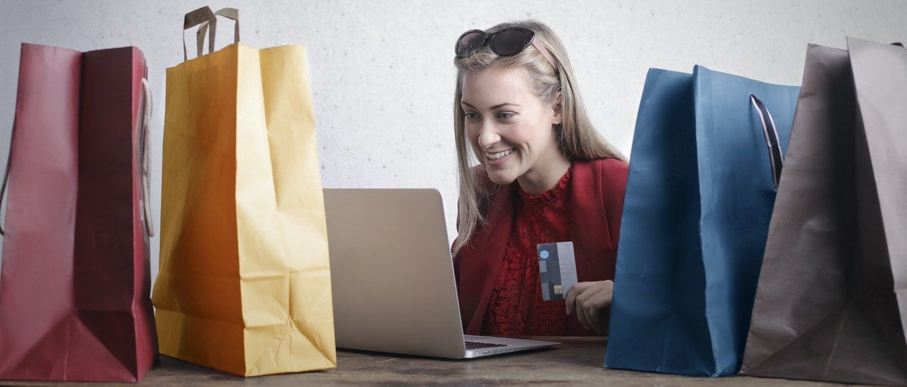 A woman sits in front of her laptop with her credit card in her hand, surrounded by shopping bags.