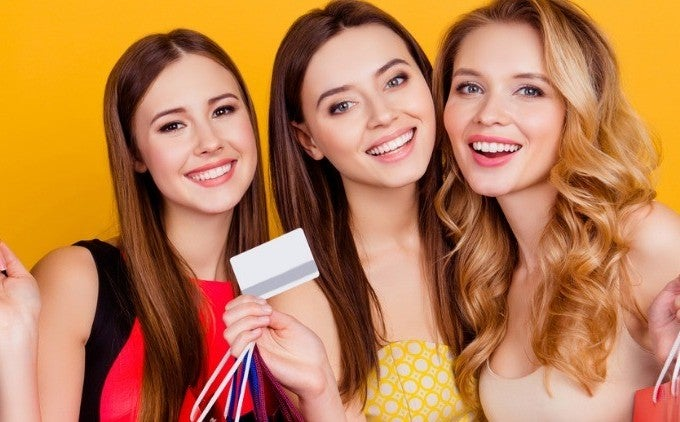 three woman with shopping bags and credit card