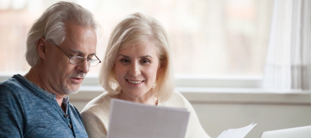 A happy elderly couple looks over the new payday loan regulations.