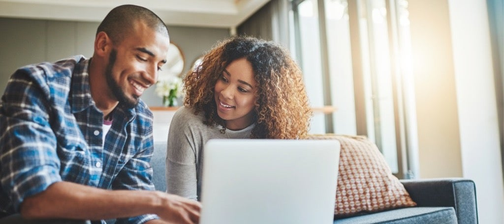 A couple pours sits in their home, applying for a low APR credit card.