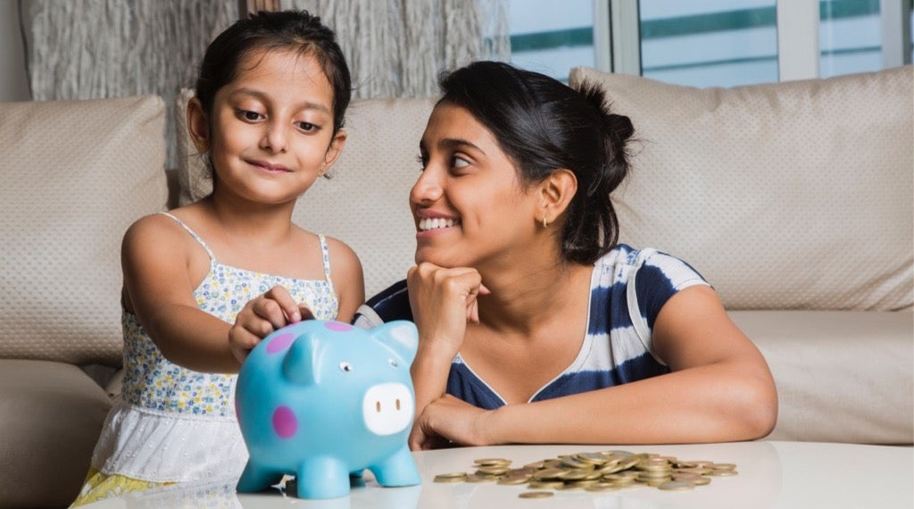 A mother teaches her daughter how to prepare for a recession by teaching her good saving habits.