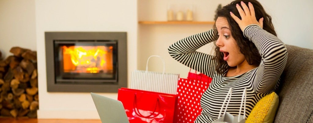 woman with shopping bags looking at online account realizing she has a maxed out credit card