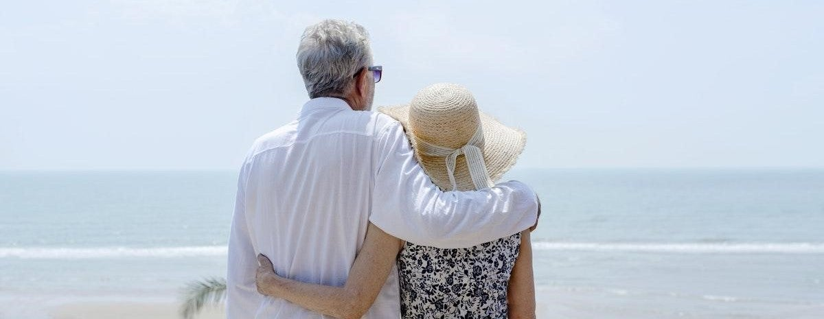 couple on beach thinking about buying a vacation home