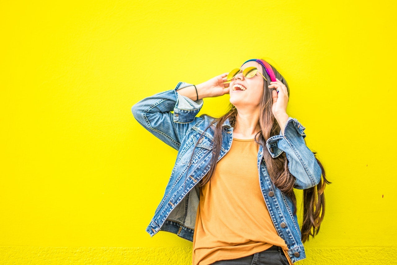 A smiling woman wearing sunglasses and a denim jacket looks up and to the side in front of a bright yellow wall