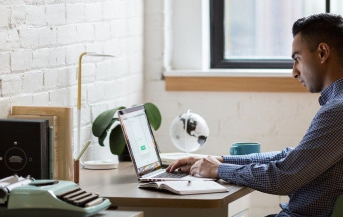 man-sitting-on-green-chair-while-using-laptop-374831