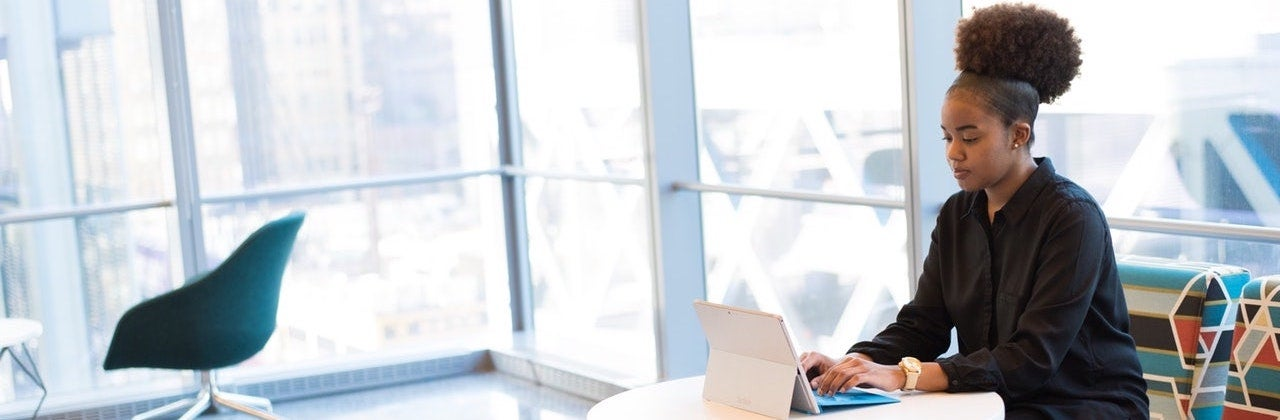 A woman with natural hair sits at a small table in front of large windows working on her tablet laptop