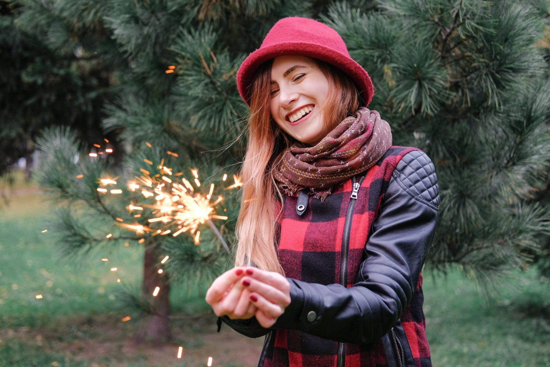 A young woman holds a sparkler and smiles because she paid off her holiday debt.