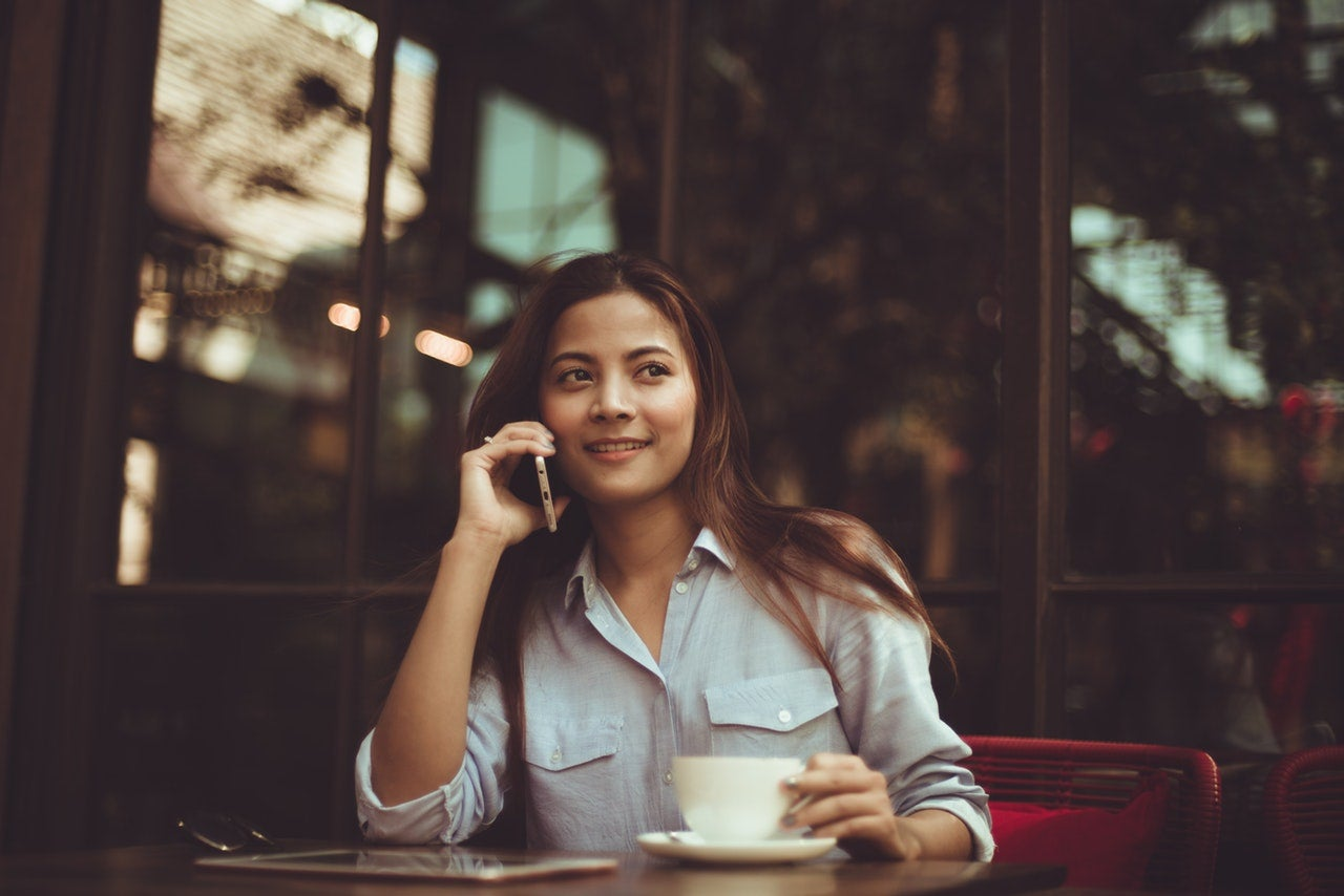 A woman speaking on the phone at a coffee shop
