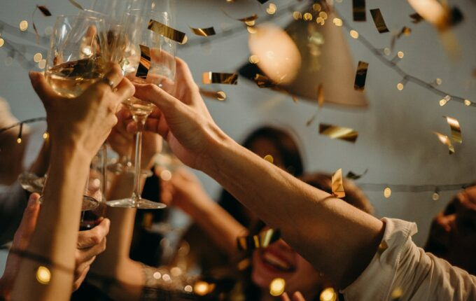 A close up of people holding wine glasses in celebration as gold confetti falls.