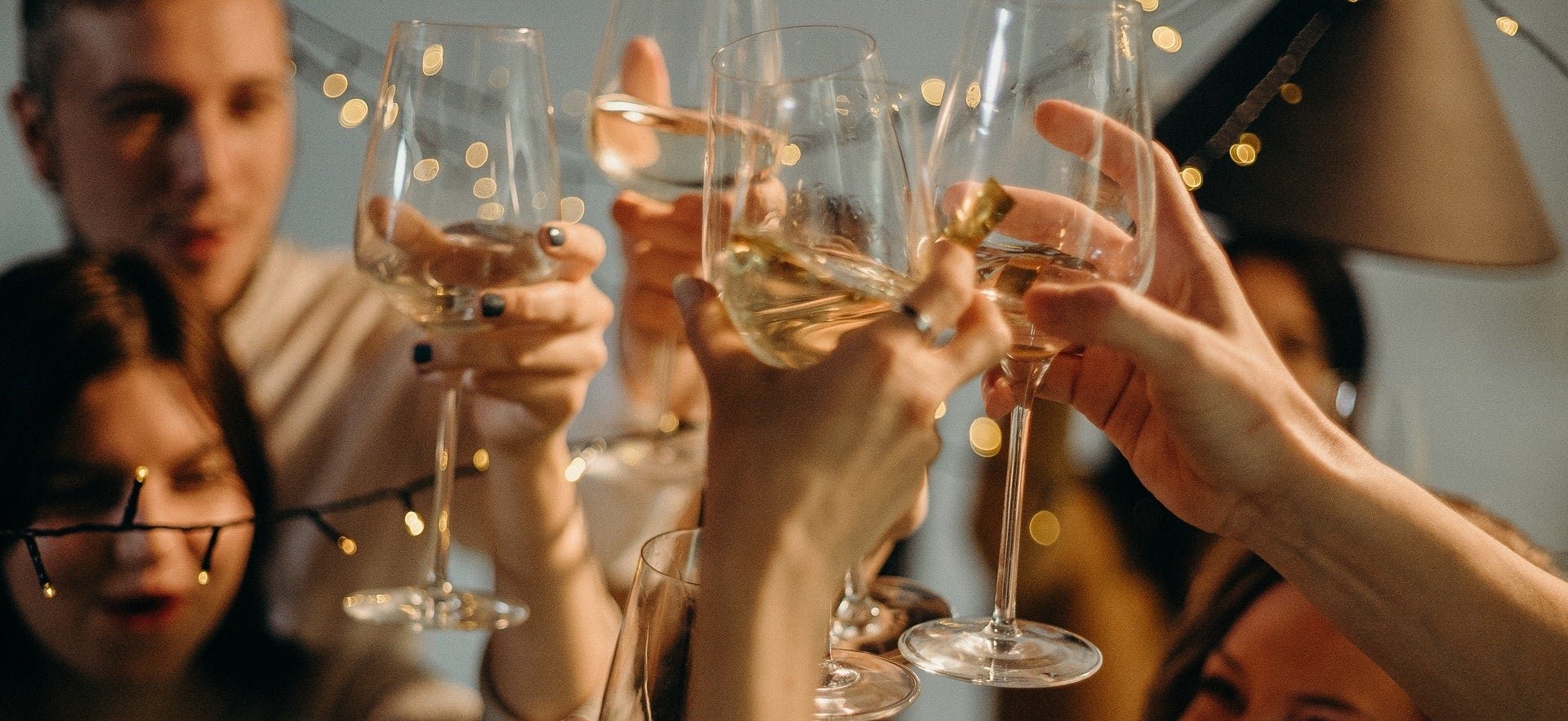 A group of friends toast with glasses of white wine