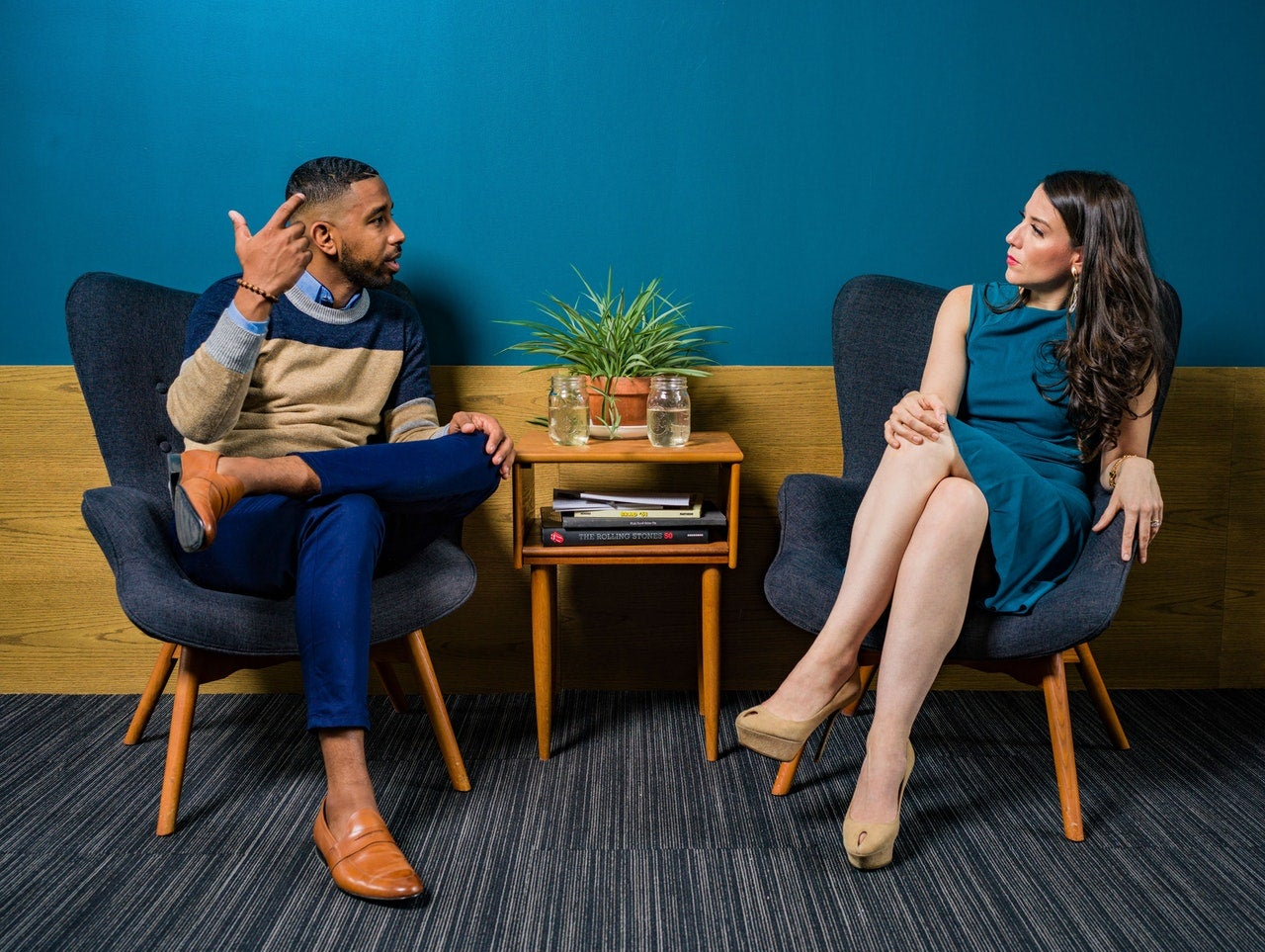 Two people sit in front of a bright blue wall having a discussion.