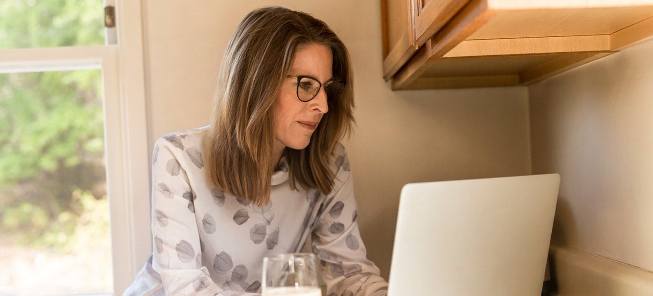 A woman leans against her kitchen counter researching the effects of COVID-19 on her laptop