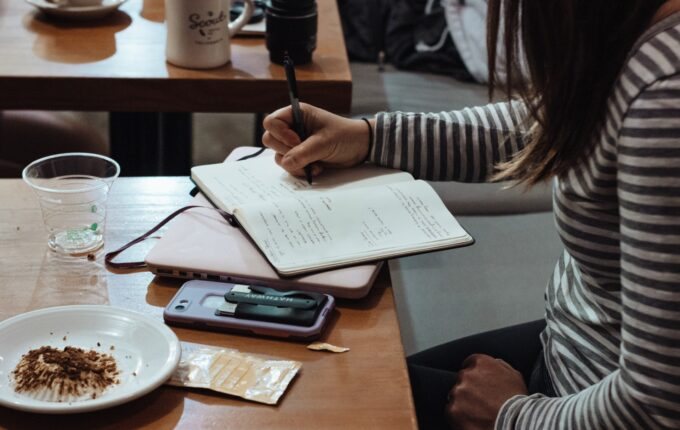 A woman wearing a longsleeved striped shirt writes in a notebook in a cafe.