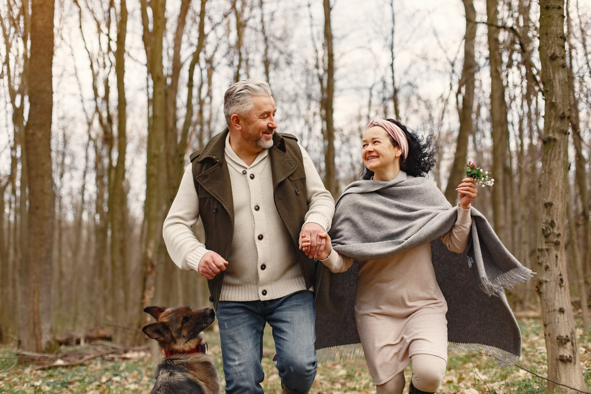 A couple holds hands in the woods with their dog, discussing tips for downsizing.