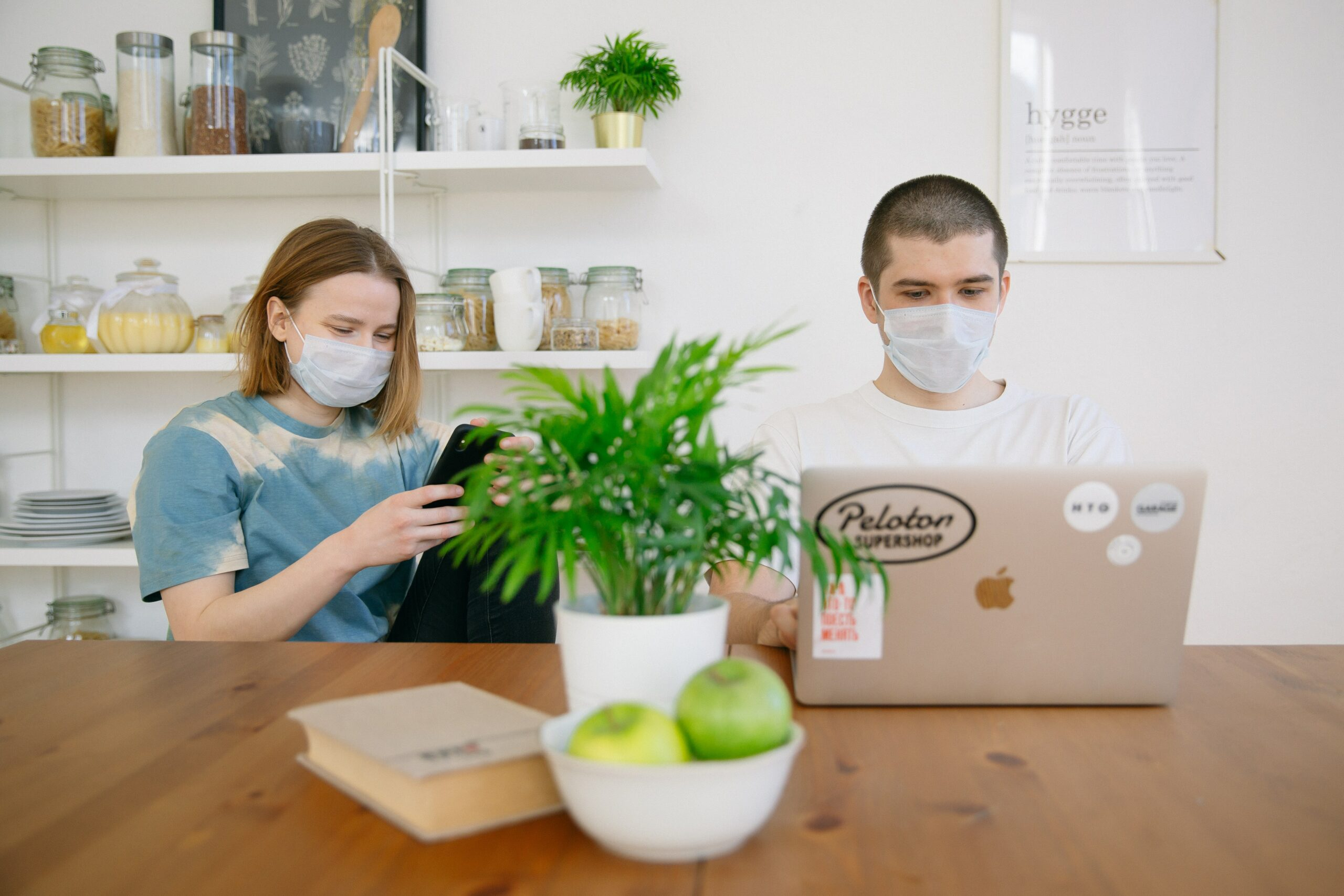 Two people in face masks sit at a kitchen table looking at their phone and laptop.