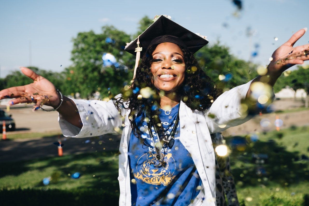A woman in a graduation cap smiles and throws confetti at the camera.