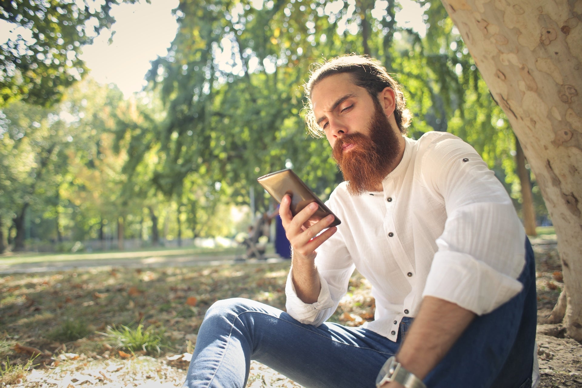 A young man with a beard sits on the ground looking at his phone considering how to become financially secure in 2020