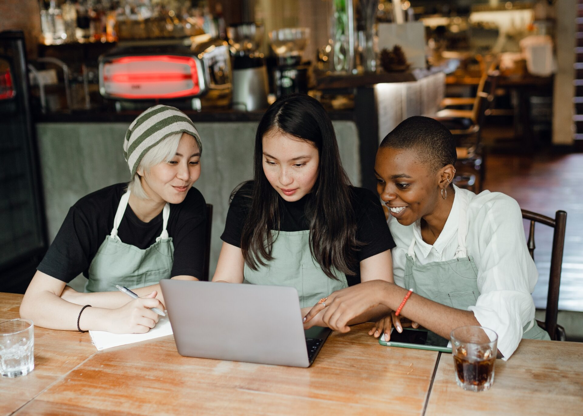 Three young colleagues wearing aprons look at FICO Resilience Index scores on a laptop