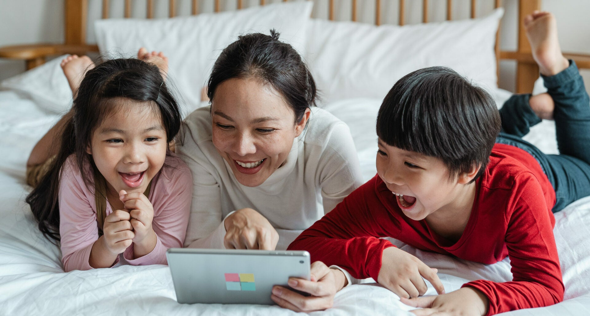 A smiling mother lays on her bed with two smiling young children. They are looking at a tablet together.