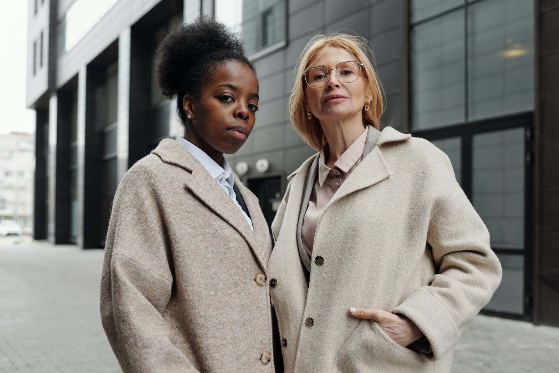 Two women look into the camera with serious looks on their faces.