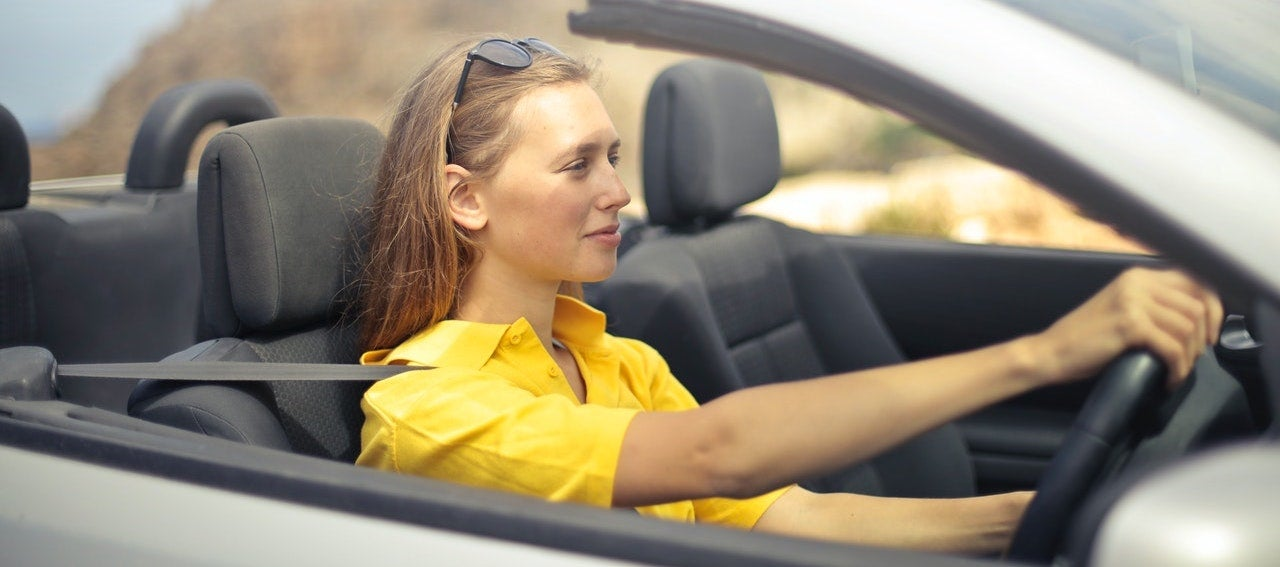 A woman wearing a yellow shirt drives a silver car.