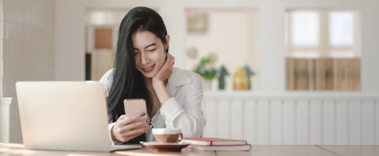 A woman sits at her desk look at at her phone.