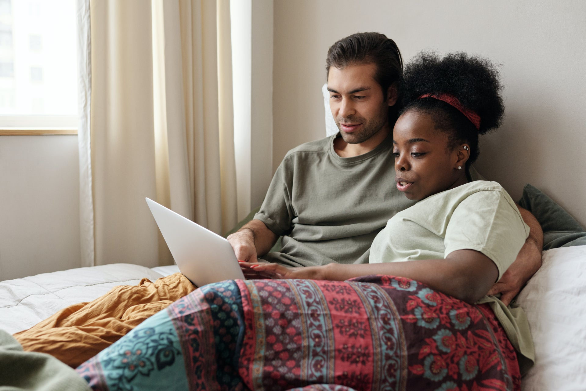 A young couple sits in bed together looking at a laptop
