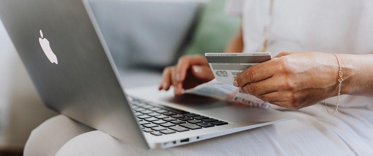 A woman has her laptop in her lap while holding her credit card in her hand.