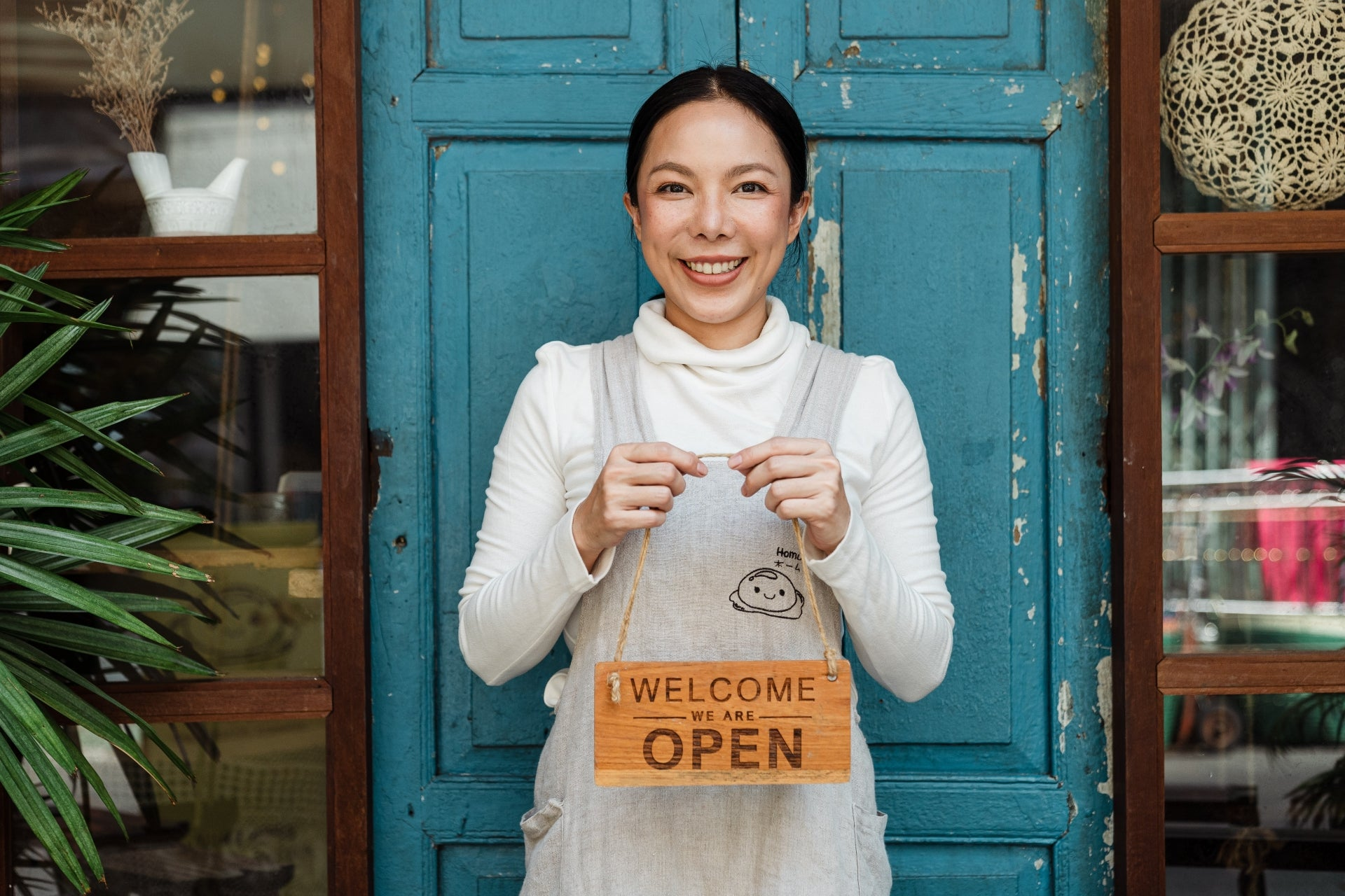 A small business owner stands in front of a teal door holding an open sign.