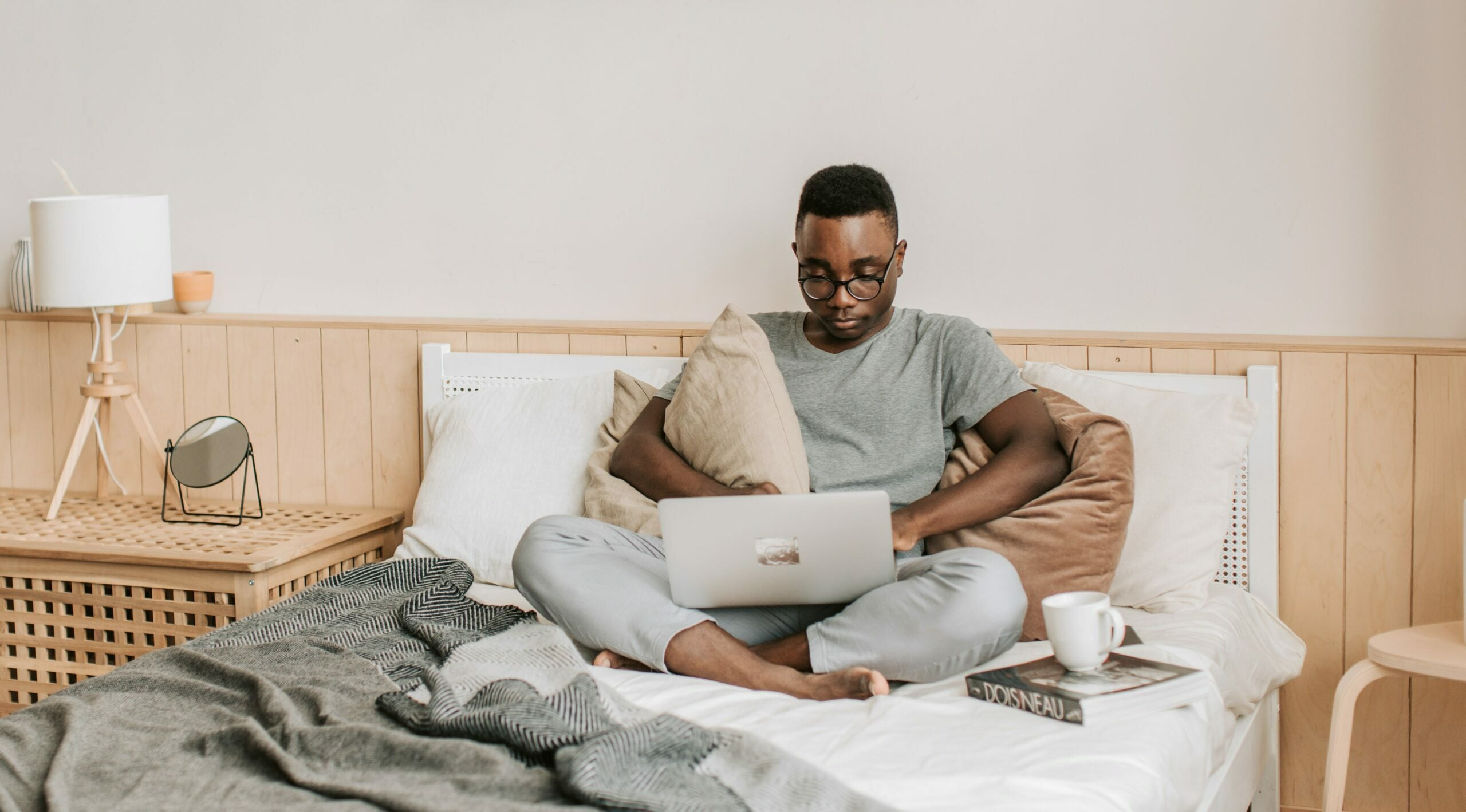 A young Black man sits crosslegged in bed on his laptop.